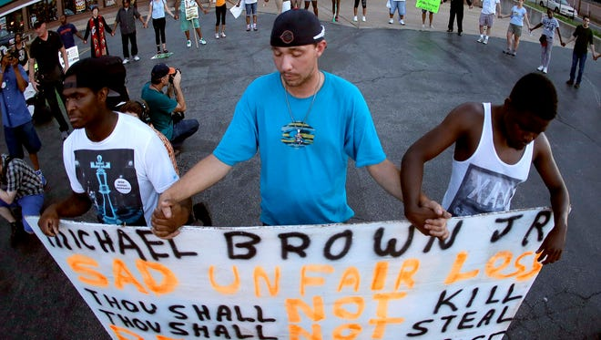People stand in prayer after marching about a mile to the police station on Wednesday to protest the shooting of Michael Brown in Ferguson. Brown's shooting on Aug 9 by a Ferguson policeman has sparked protests and riots.
