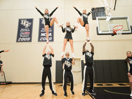 Jay Hollman, middle, practices along side UCF Cheerleaders.
