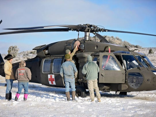 A crew of three loads their Black Hawk helicopter in