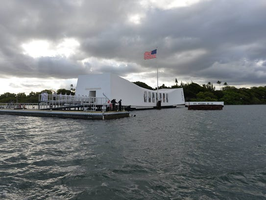 The wreckage of the USS Arizona lies beneath a white