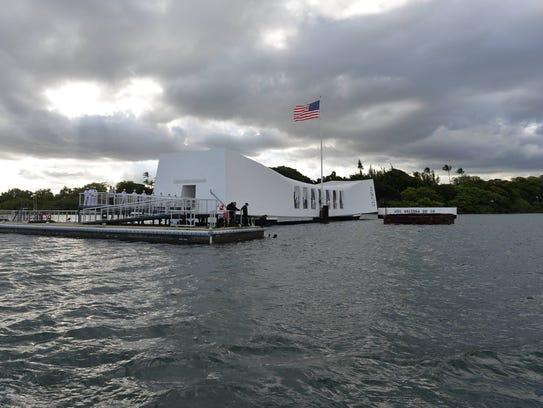 The wreckage of the USS Arizona lies beneath a white