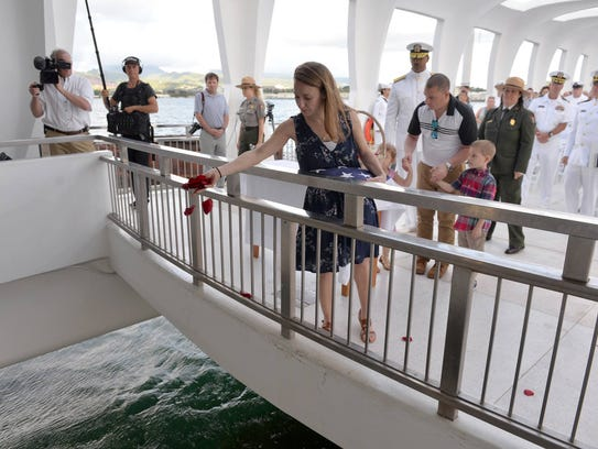 Jessica Marino drops flowers in the well of the USS