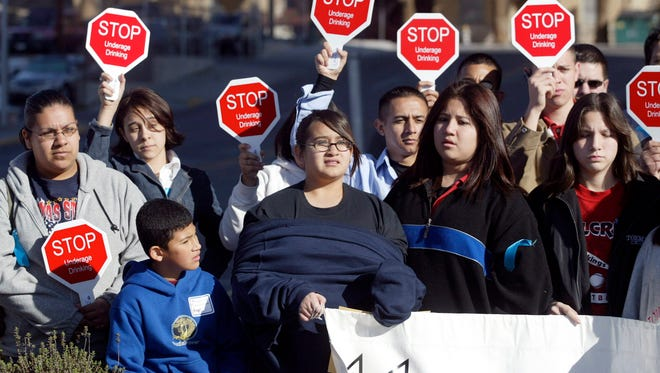 This file photo shows a group of junior high and high school students raise signs showing their support for an ordinance passed by the city council to create two special curfew zones Tuesday, March 14, 2006, in El Paso, Texas. The zones  banned people younger than 17 from the area around the two international bridges in El Paso from 7 p.m. to 6 a.m. nightly, unless accompanied by a parent, guardian or custodian. The measure is aimed at keeping teenagers from going across the bridges to Ciudad Juarez to drink alcohol.
