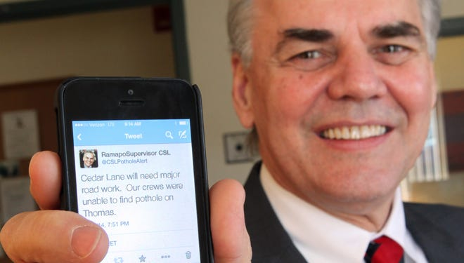 Ramapo Supervisor Christopher St. Lawrence holds his smartphone Feb. 28, 2014 with the Twitter account he and the town created that allows residents to report potholes.