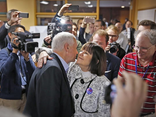 Gov. Mike Pence receives a hug from his wife, Karen, after casting their votes at St. Thomas Aquinas School.
