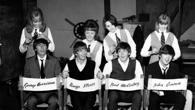 """The Beatles, George Harrison, Ringo Starr, Paul McCartney and John Lennon, have their hair combed by stylists on the set of their first movie production, """"A Hard Day's Night,"""" at Twickenham Film Studios in Middlesex, outside London, England, on March 12, 1964. The hair stylists, who had parts in the film, are Patti Boyd (from left), 19, Tina Williams, 17, Pru Bury, 22, and Susan Whitman, 17."""