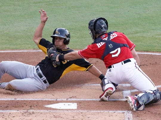 Rafael Ortega, left, of the Salt Lake Bees is tagged by El Paso Chihuahuas catcher Austin Hedges before he could touch home plate Wednesday night at Southwest University Park.