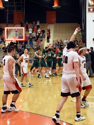 Rosecrans seniors Travis Johnston, left, Aaron Gehlken, Keagan McLaughlin and Tucker Zemba walk off the court after the Bishops' 56-55 loss to Malvern on Tuesday night in a Division IV district semifinal at Meadowbrook.