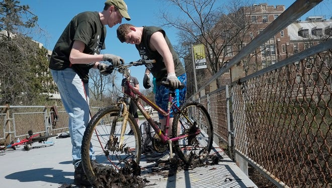 Michigan State University alumnus Matt Freechack, left, and MSU student Matthew Oxie check over a bike they pulled out of the river during the annual river cleanup on Sunday, April 17, 2016.