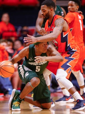 Cassius Winston #5 of the Michigan State Spartans looks to pass the ball around Mark Alstork #24 of the Illinois Fighting Illini at State Farm Center on January 22, 2018 in Champaign,