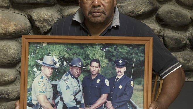 Retired Massachusetts State Police Sgt.  Albert M. Toney Jr. is photographed in his Worcester home Wednesday. He is holding a portrait of himself with his 3 sons. They are, left to right, Connecticut State Trooper Christopher Toney, Mr. Toney, Worcester Police Officer Albert M. Toney III, and Worcester Firefighter Eric Toney.