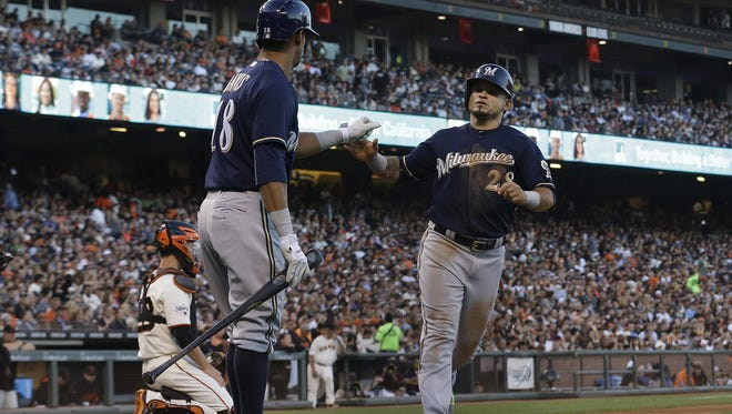 Milwaukee Brewers' Gerardo Parra (28) is congratulated by Khris Davis after scoring against the San Francisco Giants during the third inning on Tuesday.