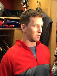 Giants quarterback Eli Manning talks at his locker