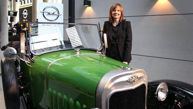 Mary Barra, new General Motors CEO, shows off an antique Opel car in a visit to the GM subsidiary's headquarters in Ruesselsheim, Germany, Jan. 27, 2014. She said GM would continue to invest in the money-losing brand.