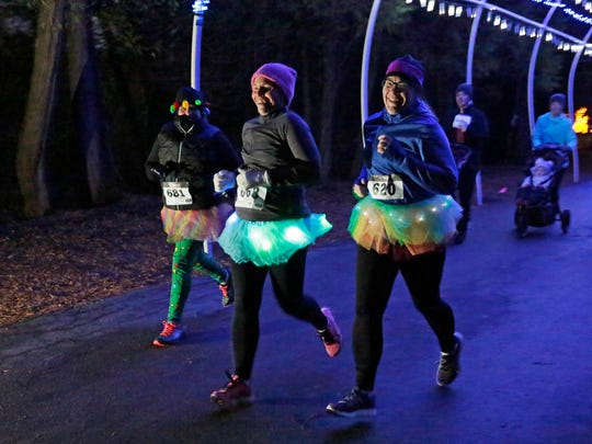 A trio of tutu wearing runners trot though holiday lights, Saturday, November 18, 2017, at Evergreen Park in Sheboygan. The event benefits The Sheboygan County Food Bank.