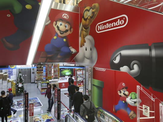 In this Nov. 15, 31, 2018, file photo, shoppers standing on an escalator passes by the logo of Nintendo at an electronics store in Tokyo.