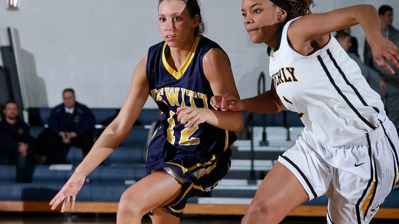 DeWitt's Maria Moss, left, drives against Waverly's Kalay Carter during their MHSAA Class A district final game Friday, March 6, 2015, in Grand Ledge, Mich. DeWitt won 53-38.