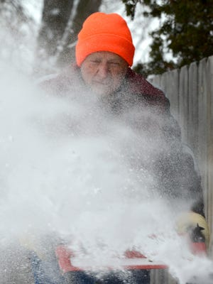 Ron Hakes deals with the wind while using a snowblower to clear a sidewalk Sunday in Allouez.