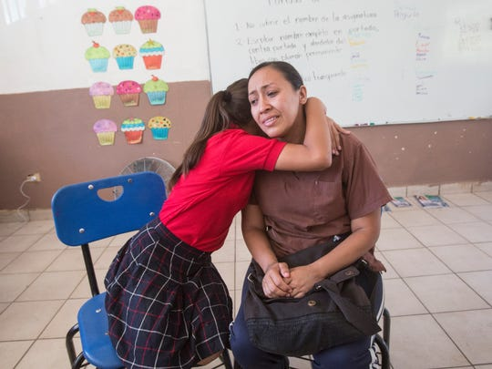 Elizabeth Rossil, 11, hugs her mother, Berenice Aguilar,