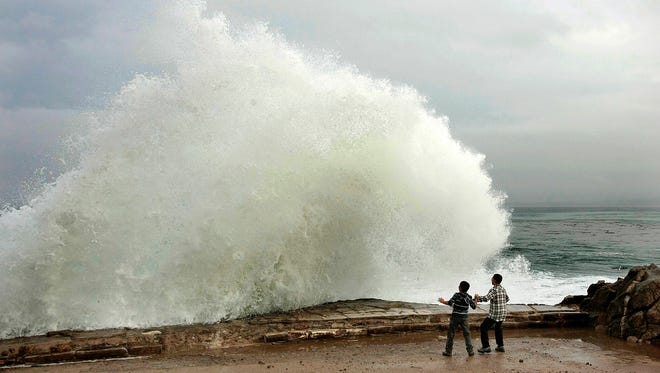 Aidan Stephenson,12, and Conor Stephenson,10, visiting from Phoenix, watch the waves break at Pacific Grove, Calif., on Wednesday. Northern California residents are bracing for a powerful storm that could be the biggest in five years and which prompted the National Weather Service to issue a high wind and flash flood warning.