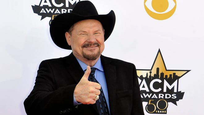 Moe Bandy giving a thumbs up on the red carpet.
