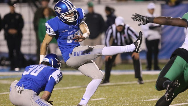 MTSU's Jim Cardwell (38) holds the ball as kicker Cody Clark (87) makes the extra point after the overtime touchdown during the NCAA college football game against Marshall  Saturday, Nov. 7, 2015, in Murfreesboro.