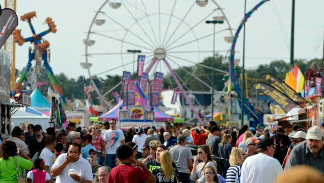 Crowds make their way along the midway during the last day of the York Fair, Sunday September 15, 2013. Longtime fair director Cres Ottemiller died Tuesday. He was 87.