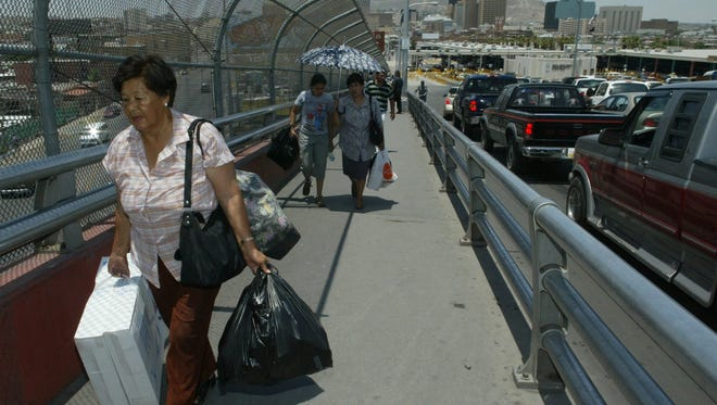 Maria Martinez of Chihuahua City crosses back into Mexico on the Paso del Norte Bridge carrying goods, including two box fans, she bought in El Paso stores. More than two decades after the adoption of the North American Free Trade Agreement, controversy continues.