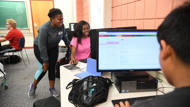 Danielle Staggers, left, Furman Bridges to a Brighter Future assistant director for college success, helps Kourtney Hinton on a presentation for a college planning course on Thursday.