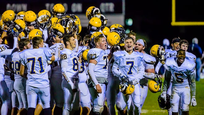 Members of the Grand Ledge football team celebrate after their 31-28 win over East Lansing Friday October 14, 2016 in East Lansing.