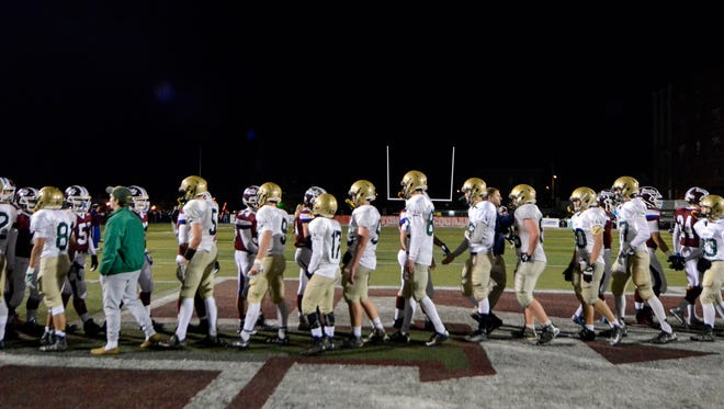 Members of the York Catholic football team shake the hands of Dunmore players after Friday night's state playoff loss. The seniors on the Fighting Irish played their final game for the program. John A. Pavoncello photo