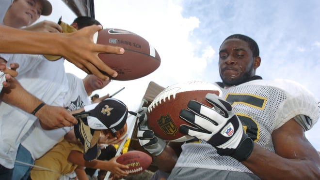 Running back Reggie Bush draws a crowd of autograph seekers after practice on Friday during the 2008 Saints training camp at Millsaps College in Jackson.