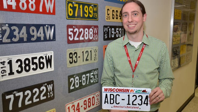 Jeremy Krueger, plate room supervisor for the Wisconsin Department of Transportation, holds an example of the state's new seven-digit license plates.