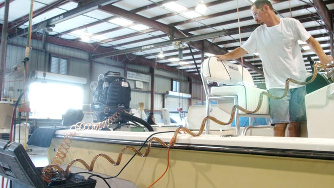 Jack Cayson bleeds the hydraulic in the lifts for the outboard motor and checking the electronic in 2007 at Maverick Boats in Fort Pierce.