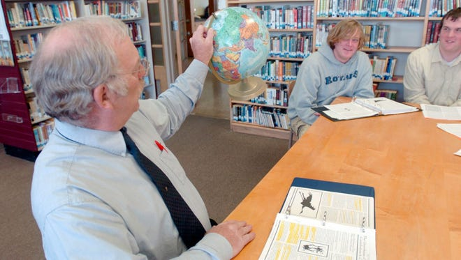 Paul Klinkhammer, then a teacher at Assumption High School, works with students in this 2007 file photo. Klinkhammer was reinstated as Assumption High School prinipal following an investigation into a report he made a bomb threat against a textbook publisher.