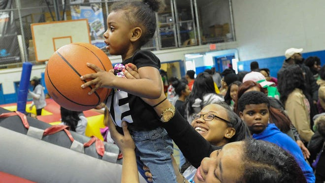 """Delaware State University freshman Jordan Washington (right) and Taijera Rogers help Naya Scott, 2, of Dover shoot a basket at the Greater Boys and Girls Club in Dover as part of university's fourth annual """"Inspired Day of Service"""" at seven locations statewide."""