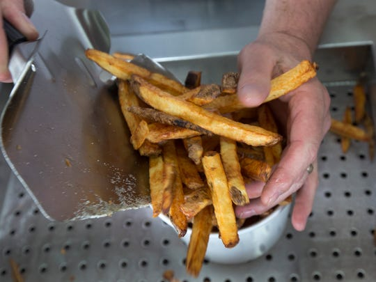 Desmond Hussey of Kuppers French Fries in Seaside Heights scoops a fresh batch of fries into a cup.
