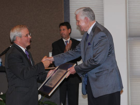 Northwestern State University President Randall J. Webb presents President-elect Jim Henderson with a framed certificate at a news conference on the Natchitoches campus on Wednesday.