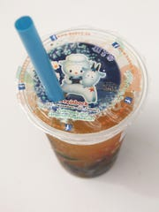 A cup of mango-flavoured bubble tea stands at a bubble
