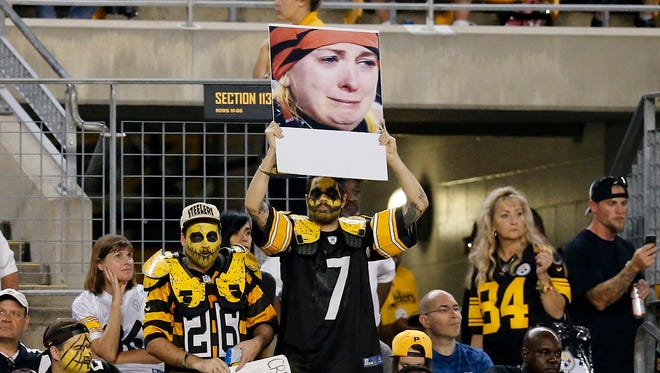 """Pittsburgh Steelers fans hold up a sign of the infamous """"Crying Bengals fan"""" during the fourth quarter."""