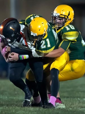 Olpe defenders Gabe Castillo (21) and Jordan Barnard (10) smothered a Lyndon back during last Friday's Class 1A semifinal game. Olpe's defense has allowed just 35 points this season, fewest of any team in the state.