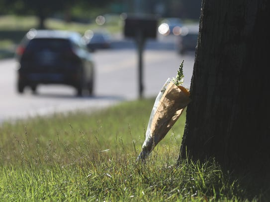 Flowers are left on the side of a road near the area