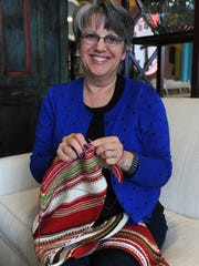 """Wendy Shepherd adds rows of red to her """"mood scarf"""" at Leon & Lulu in Clawson."""