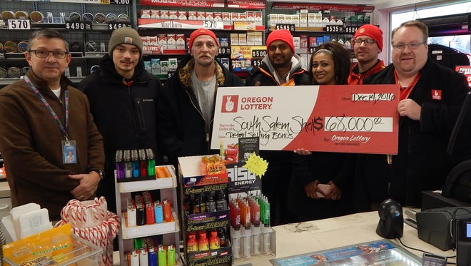 Oregon Lottery officials and staff and owners of the South Salem Shell station celebrate the retailer selling bonus for selling the $6.8 million winning Megabucks ticket in November. Pictured from left to right, Oregon Lottery Field Sales Representative Curtis Grassman, station attendants Jacob Stobbe and Tim Cowan, station owners Sanjay and Praveena Prasad, station attendant Kyle McGuire, and Oregon Lottery Winner and Promotions Specialist Patrick Johnson.