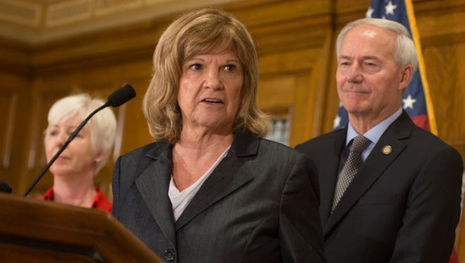 Division of Youth Services Director Betty Guhman (center) is  flanked by DHS director Cindy Gillespie and Governor Hutchinson at a recent news conference.