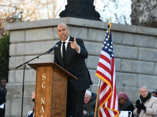 Sen. Cory Booker, D-N.J., speaks as Sen. Bernie Sanders, I-Vt., third from right, and others listen during Martin Luther King Jr. Day celebrations at the South Carolina Statehouse in Columbia, S.C., on Monday, Jan. 21, 2019. (AP Photo/Meg Kinnard)