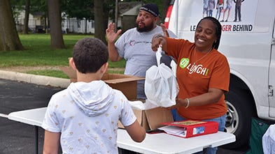 Children's Hunger Alliance staff distribute food at a mobile meal stop.