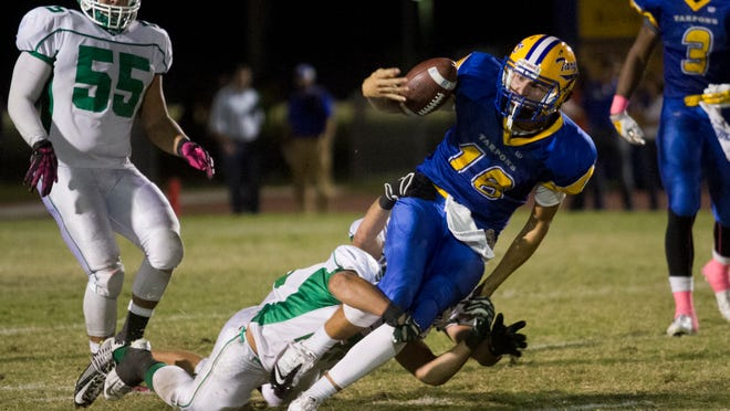 Fort Myers' Zach Lecius and Jake O'Rourke take down Charlotte High quarterback Brennan Simms on Friday, October 17, 2014, in Punta Gorda.
