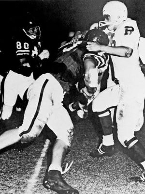 Bill Dawson, plowing into a Rincon High School player in this 1966 photo, was the Arizona football player of the year while helping Tucson High win the state title in 1966.