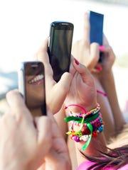 Teens holding smartphones